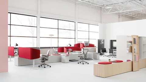 An open office in an industrial building with gray Aeron Chairs at sit-to-stand Locale workstations with red privacy screens.