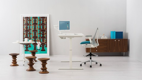 A modern office featuring a white Augment Ratio height-adjustable desk and blue Sayl Stool, both viewed from the side.