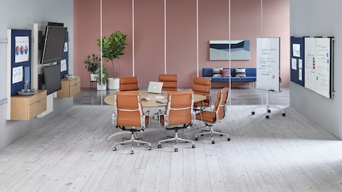 Six burnt-orange Eames Soft Pad Chairs surround a teardrop table in a collaboration area featuring Exclave display elements.