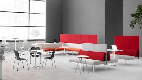 A social and collaboration space featuring Caper Stacking Chairs, Setu Stools, and Public Office Landscape seating in orange, red and white.
