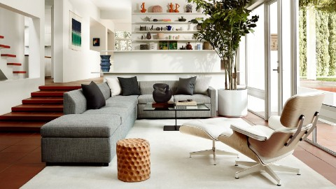 A vingette of furnishings from the Herman Miller Collection, including an L-shaped Bevel Sofa in grey and an Eames Lounge Chair and Ottoman in white.