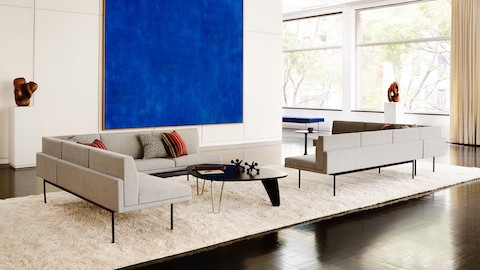 Two ivory-colored Tuxedo sectionals provide lounge seating in a bright space with large blue wall art.