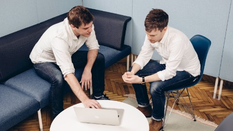 Two men look at a laptop in a Living Office Cove Setting. One is sitting on a blue Public Office Landscape couch and the other is sitting on a blue Eames Shell Chair.