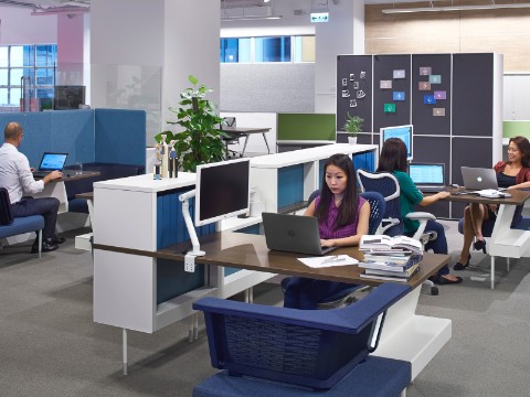 People working at computers in a Hive Setting furnished with Public Office Landscape in blue and white, and with blue Mirra 2 Chairs.