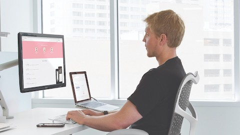A casual office worker achieves correct ergonomic posture with a gray Mirra 2 chair and a Flo Monitor Arm.