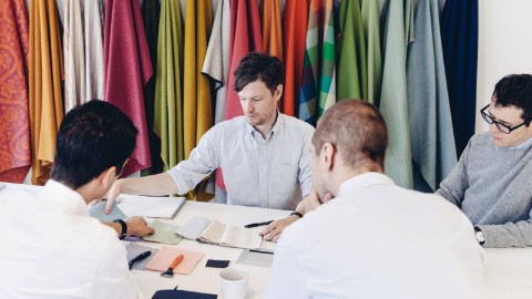 Four businessmen around a table examine various brightly colored fabric swatches.