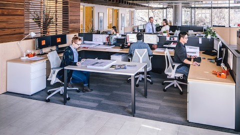Three men and three women work in an open office environment that features white Sayl office chairs.