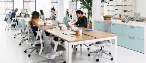 A handful of colleagues work independently in an open office that features a benching setup with light grey Sayl office chairs.