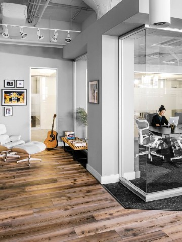 Woman working in a glass-walled office with Eames Lounge Chair and Ottoman nearby.