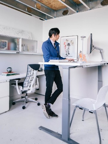 Man working on a computer while standing at a Renew Sit-to-Stand Table.