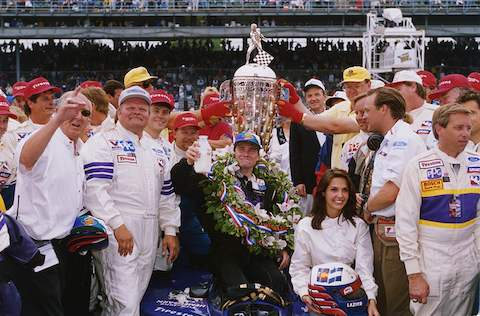 1996 Indianapolis 500 winner Buddy Lazier poses in victory lane with members of the Hemelgarn Racing team and his wife, Kara Lazier. His injured back made it too painful for him to stand during the celebration, so he received his ceremonial bottle of milk while seated on his car.