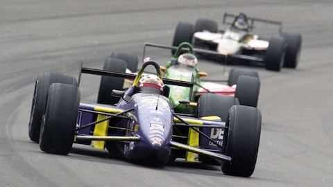 Two Indy cars on a racetrack. Select to read an article about the link between auto racing and Herman Miller work chairs.