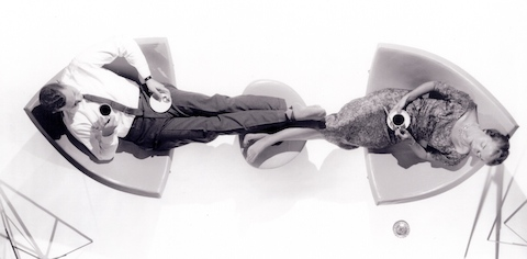 A man and a woman relaxing in a pair of Nelson Coconut Lounge Chairs while sharing an ottoman.