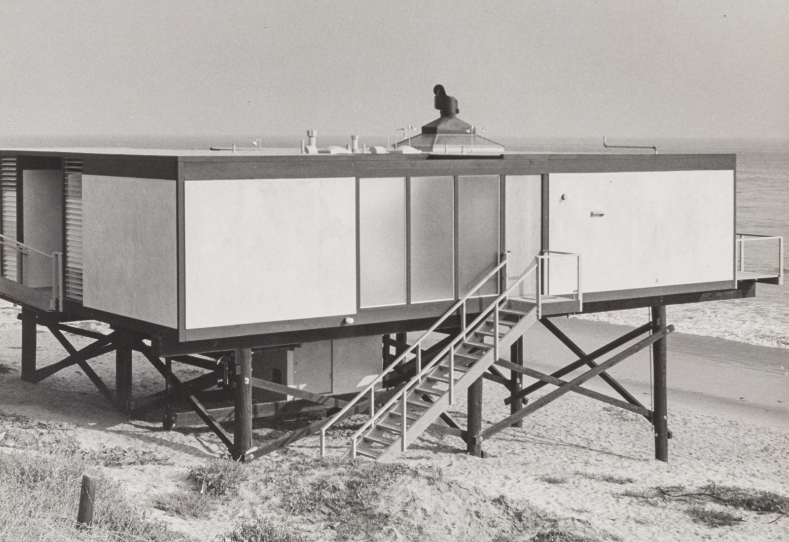 Exterior view of Craig Ellwood's Hunt House showcasing its setting on stilts on the beach in Malibu, California.