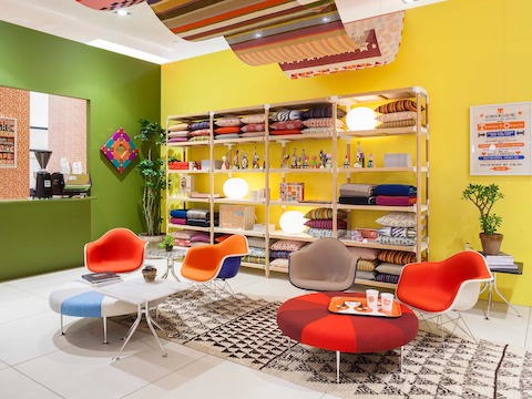 Girard's Color Wheel Ottomans and Eames Upholstered Molded Fiberglass Arm Chairs form the basis of a Girard-inspired living room.