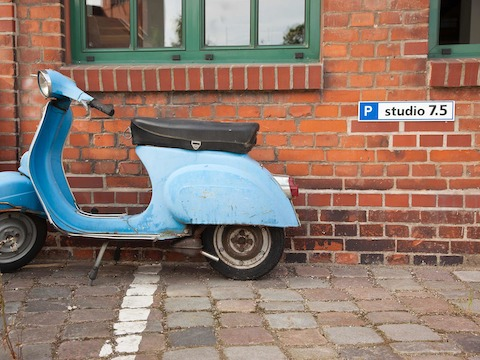 A vintage blue motorbike parked alongside the exterior brick wall of Studio 7.5 in Berlin.