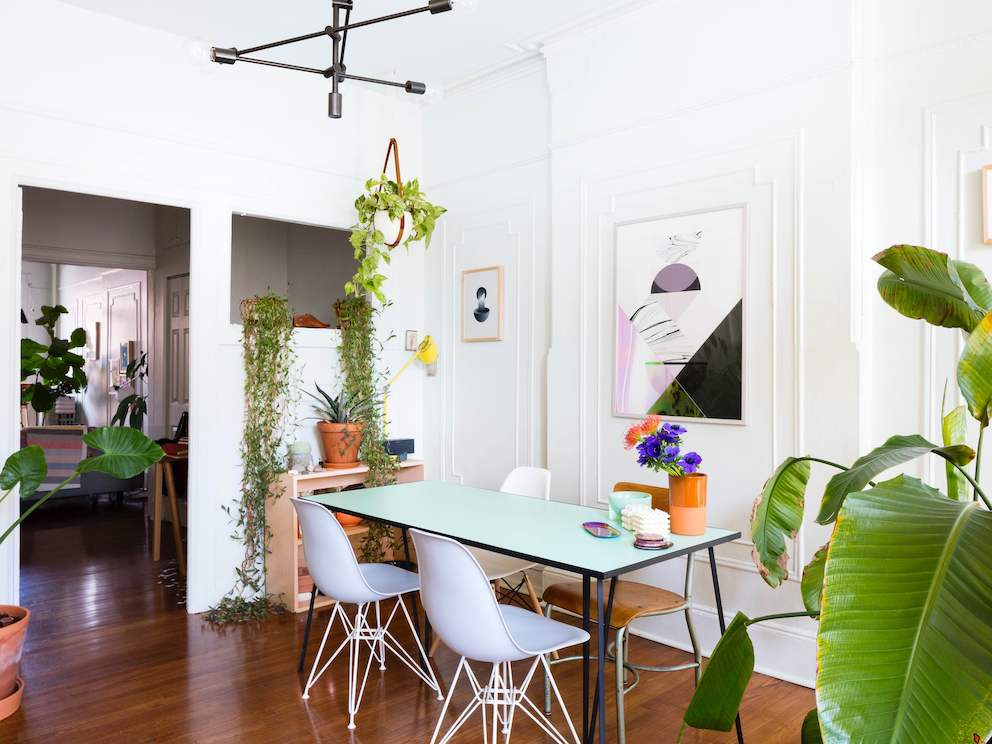 A residential dining area featuring a rectangular table, white Eames Molded Plastic Chairs, modern artwork, and plants.