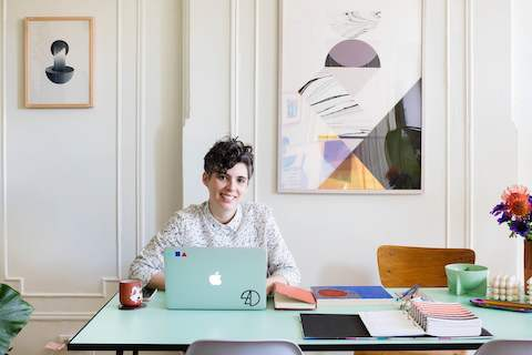 Designer Alex Proba works on her computer while sitting at a table in her home.