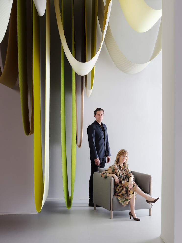 Designers Stefan Scholten, standing, and Carole Baijings, seated, next to hanging textiles.