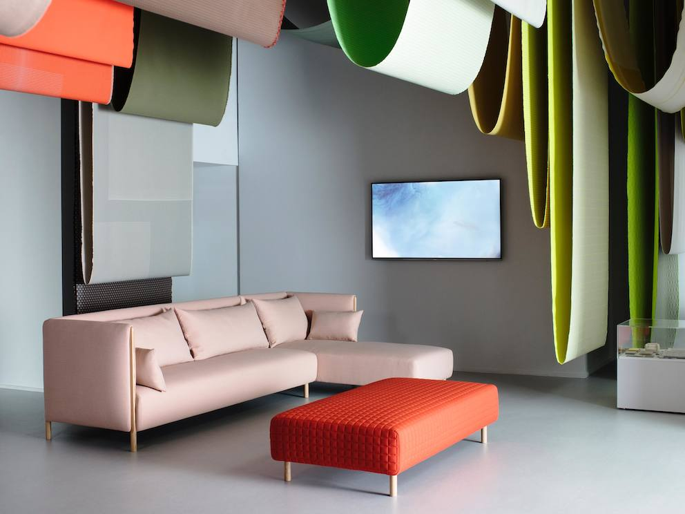 A pink ColourForm sectional and a red ColourForm ottoman beneath hanging textiles of various colors.
