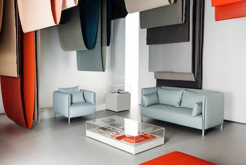 Blue ColourForm seating beneath hanging textiles of various colours.