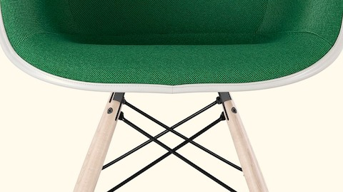 Close view of an Eames chair with green upholstery. Select to read an essay about Charles and Ray Eames and quality.
