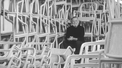Designer Ward Bennett sits among dozens of stacked chairs. Select to go to an article about Bennett.