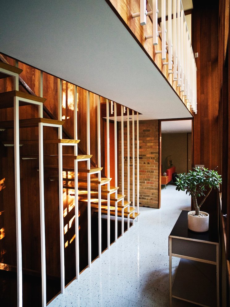 A staircase with treads cantilevered from the redwood wall and suspended by a bank of ceiling-height balusters.