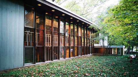 The exterior of a modern house with a wall of windows. Select to read an article about a home designed by George Nelson.