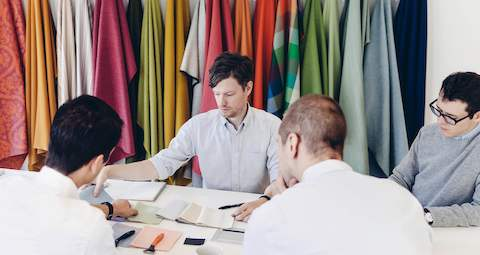 Four seated men review fabric samples. Select to go to an article about shaving company Harry's move to a Living Office.