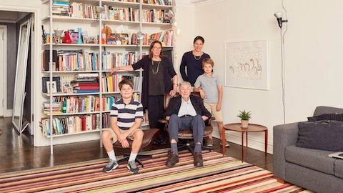 Five family members pose near a bookcase. Select to go to an article about one family's experience with an Eames Lounge Chair and Ottoman.