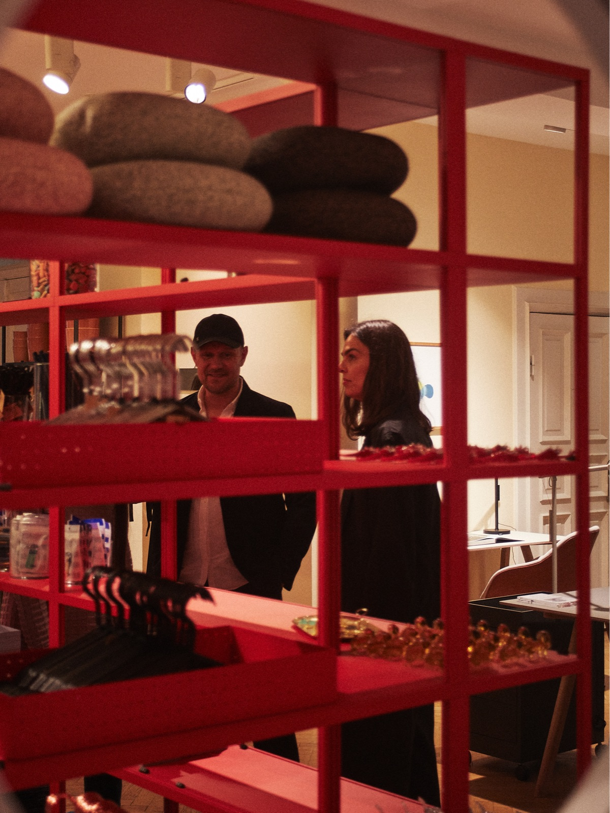 Rolf and Mette Hay are seen in their flagship store, HAY House, through a red shelf dotted with accessories.