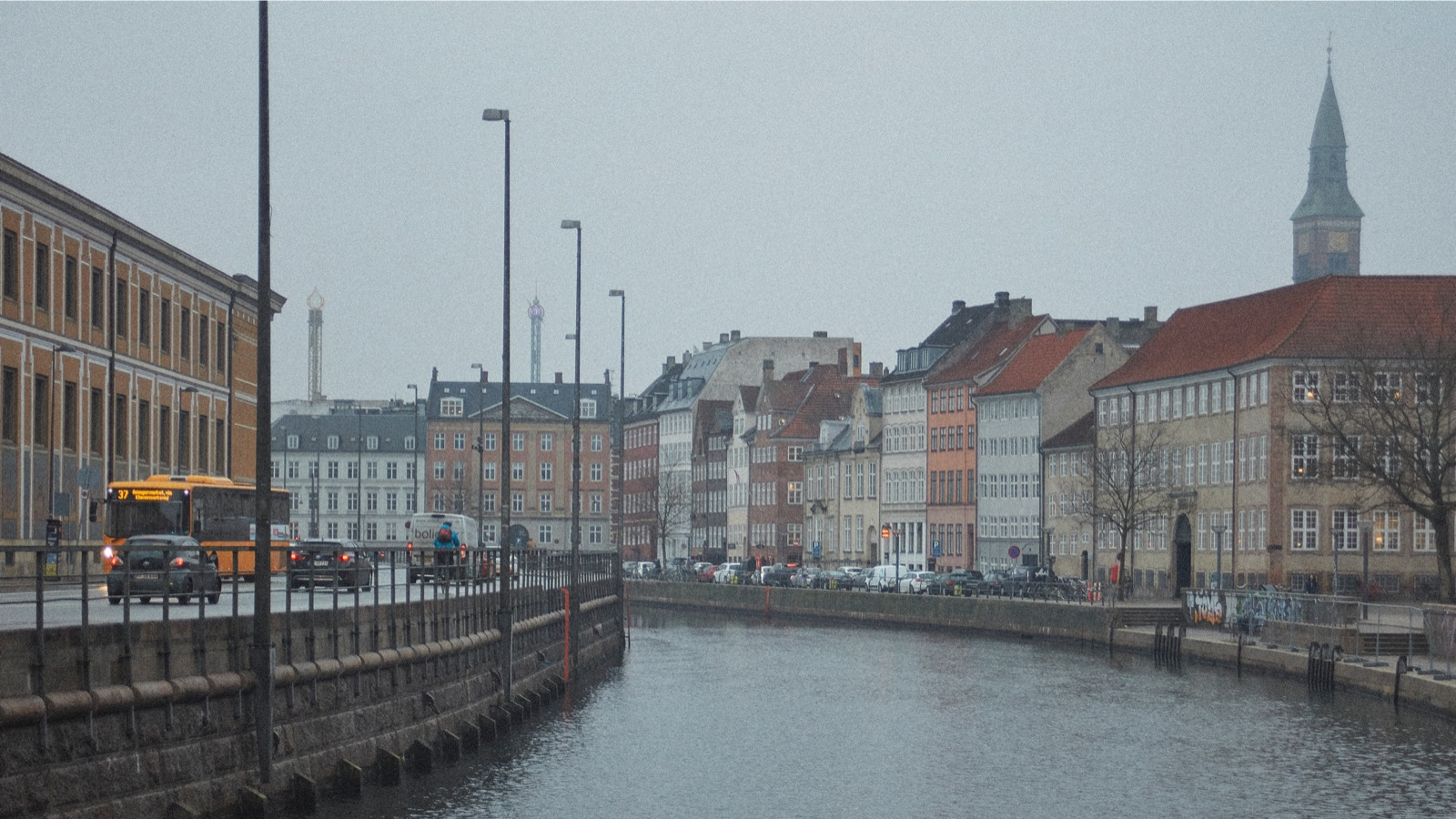 A river on a rainy day in Copenhagen, with buildings on the right and a road on the left.