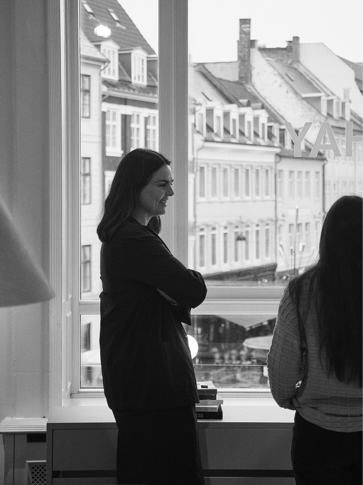 A black and white photograph of Mette Hay, shown from the side, and the back of Amy Auscherman at HAY House in Copenhagen.