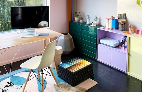 The home office of artist/designer Alex Proba includes a simple desk and chair with a view of nature, and colorful storage units along a wall.