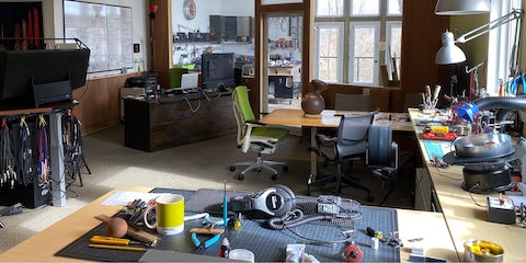 Designer Brian Alexander's home studio with a large desk, tools, parts for his designs, a laptop and monitor, and a green Embody Chair.