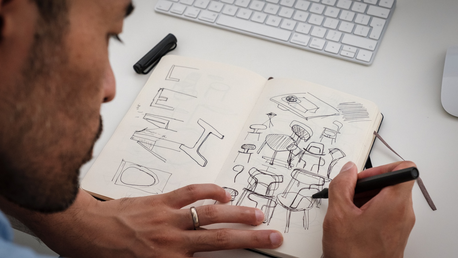 Japanese-born designer Keiji Takeuchi sits at the desk in his home studio in Milan, Italy and sketches ideas for a chair design in a notebook.