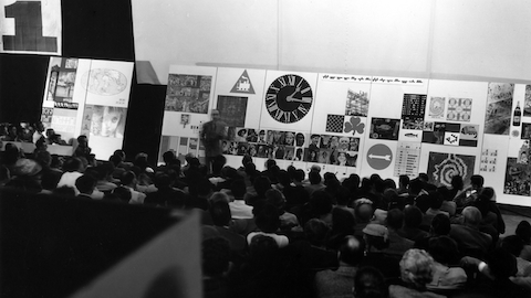 A man speaks before a seated crowd. Select to read an article about a 1952 lecture by George Nelson, Charles Eames, and Alexander Girard.