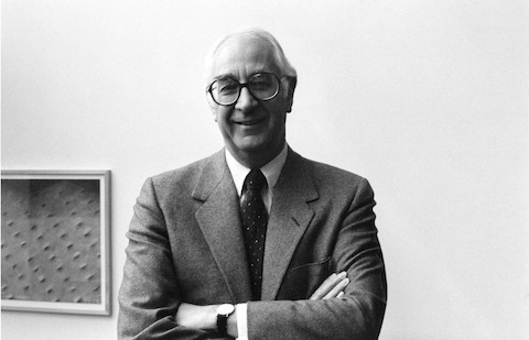 A black-and-white image of former Herman Miller CEO Max De Pree with arms crossed.