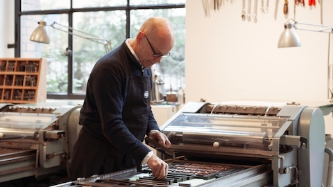 A man works with a printing press. Select to go to an article about the typeface used as Herman Miller's corporate font.