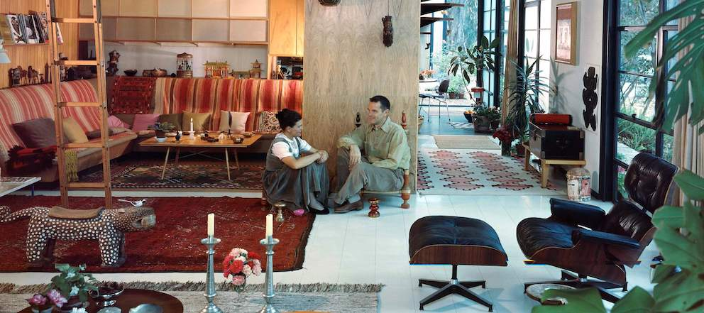 In this color photo, Charles and Ray Eames sit on the floor in their living room. They are surrounded by an Eames Lounge Chair and Ottoman and objects from their travels.