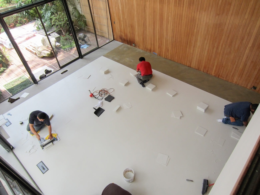 A color photo of a bird's eye view of three men sitting on a covered floor in the Eames House living room. They use tools to work on repairs to the space.