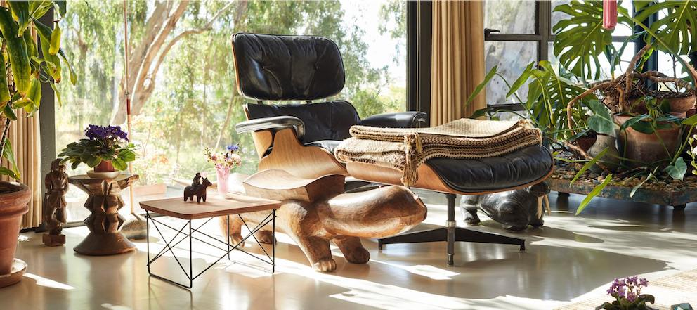 A color photo of a black leather Eames Lounge Chair and Ottoman in the living room at the Eames House. A tan blanket is folded on the ottoman, and a LTR table sits nearby.