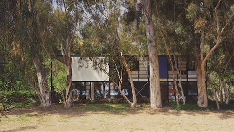 This color photos is a view of the Eames House from the front, showing off white, blue, and red panels. Eucalyptus trees and flowers line the front of the house.