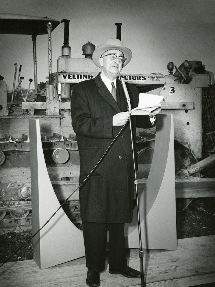 Herman Miller founder D.J. De Pree speaks into a microphone and stands before heavy machinery at a building site.