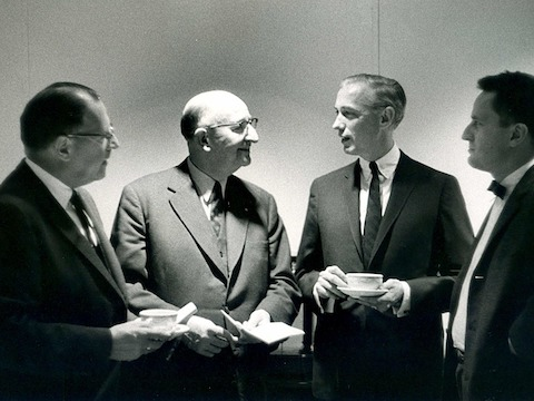 A black-and-white photo of Herman Miller founder D.J. De Pree with three colleagues.