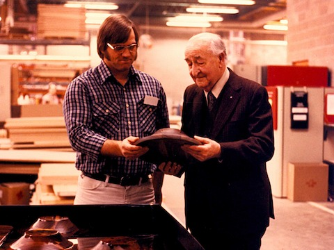 A color photo of Herman Miller founder D.J. De Pree interacting with a factory worker on the plant floor.