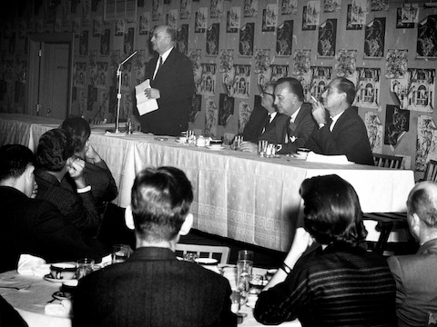 A black-and-white photo of Herman Miller founder D.J. De Pree standing behind a head table and speaking at a professional gathering.