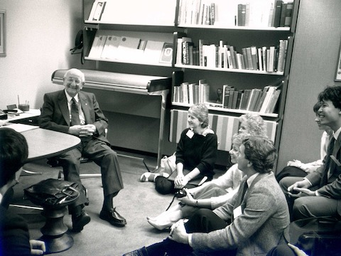 A black-and-white photo of Herman Miller founder D.J. De Pree chatting informally with a group of young people.