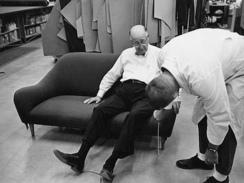 Herman Miller founder D.J. De Pree tries out a sofa while an employee takes measurements.